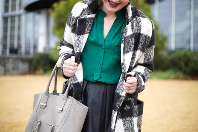 Faux leather pleated skirt, black and white plaid coat, green blouse, black booties, top knot, metallic tights, berry lip